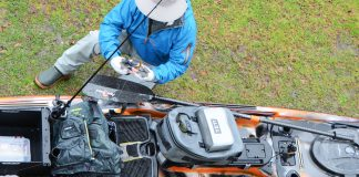 Overhead view of angler getting fishing kayak ready on land
