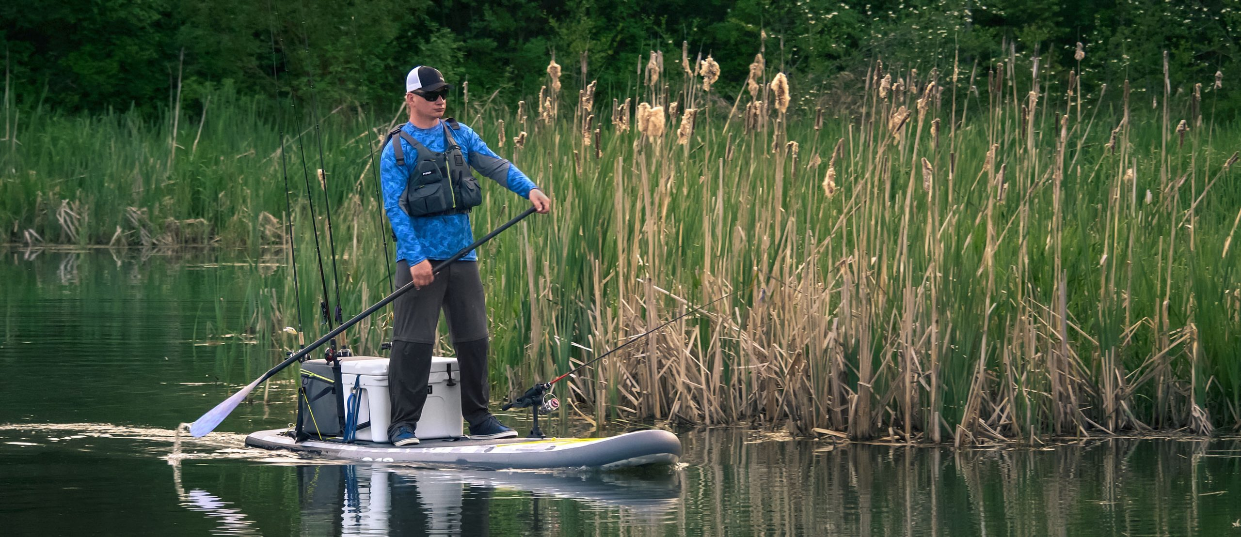 Man standing on paddleboard with fishing rods and cooler behind him.
