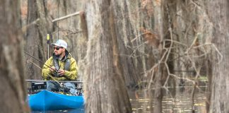 Man fishing from kayak in the trees