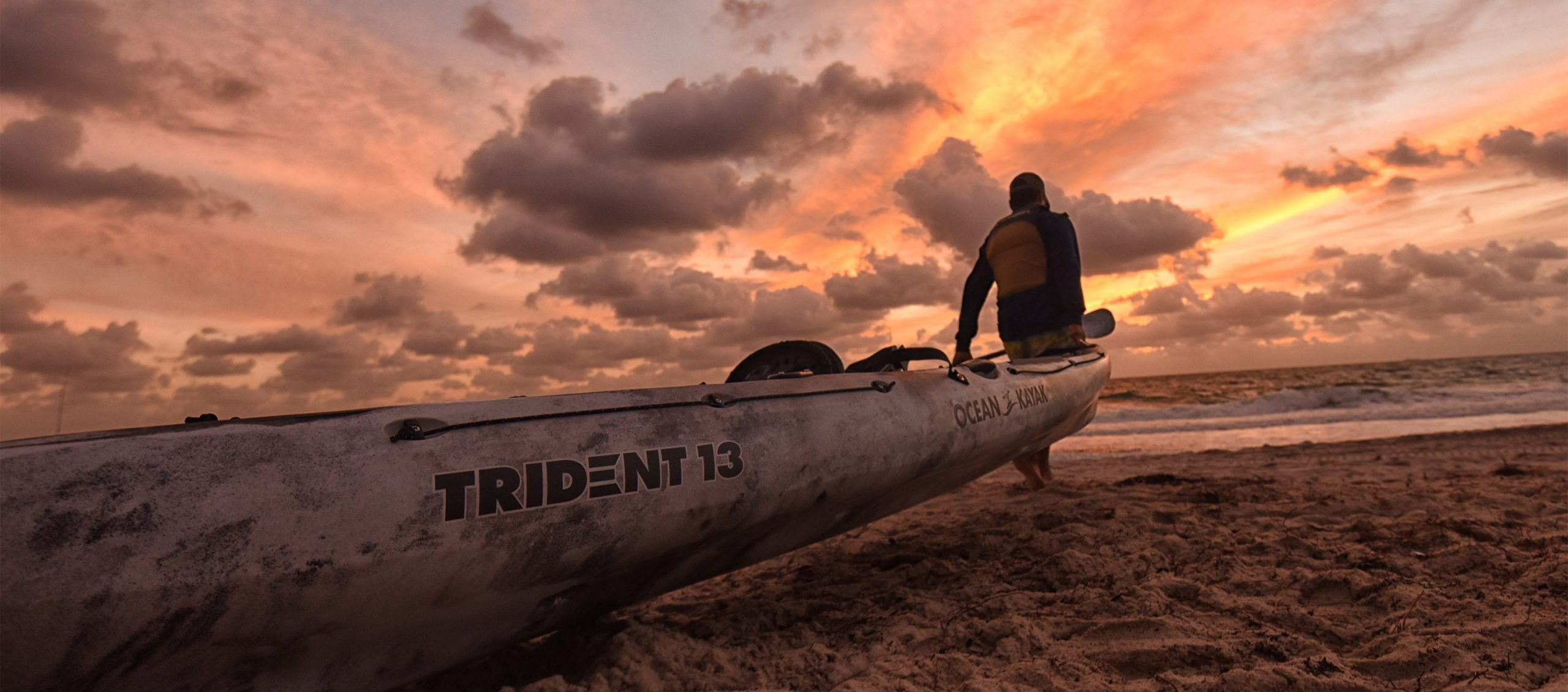 Person dragging a sit-on-top fishing kayak over sand toward water