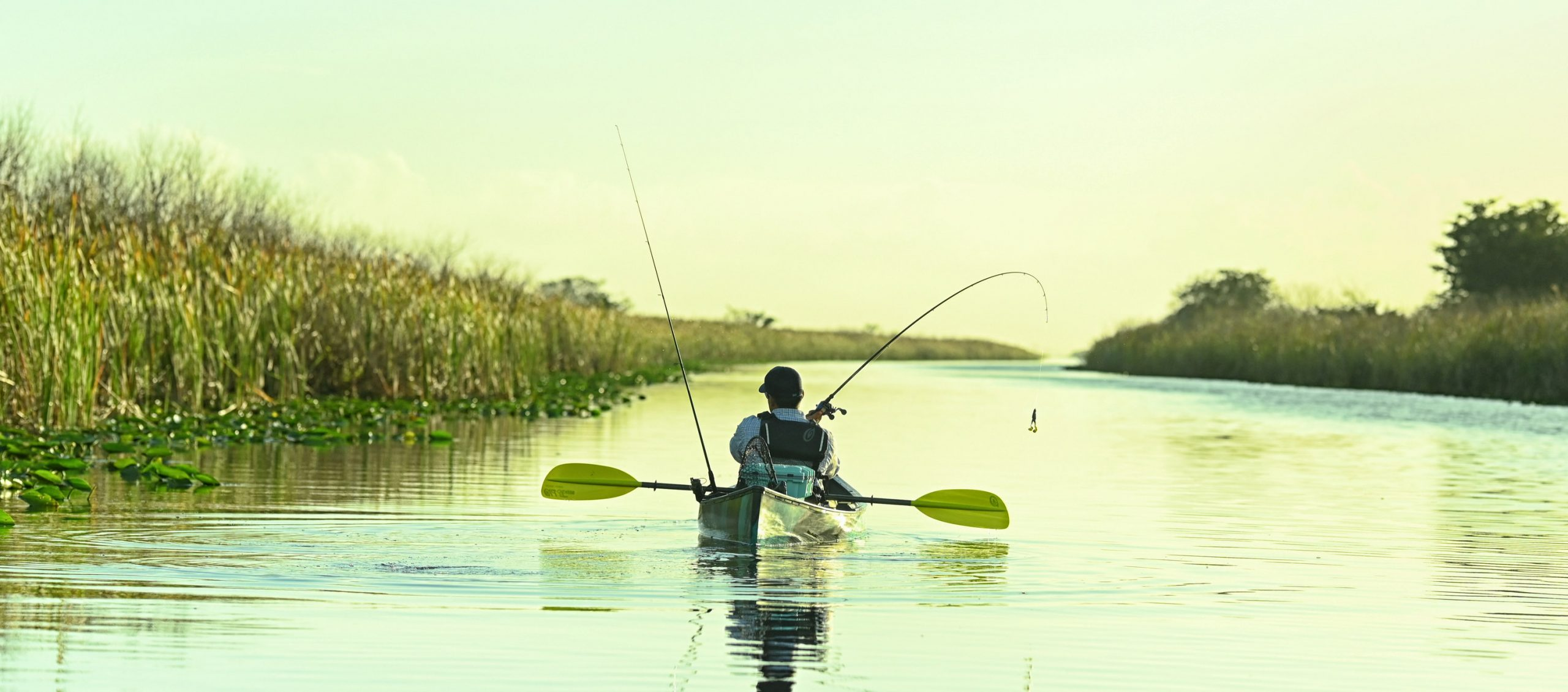 Person fishing from kayak with paddle