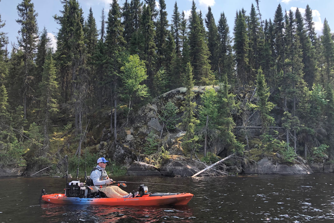 Kayak Angler paddles along rocky short for smallmouth bass