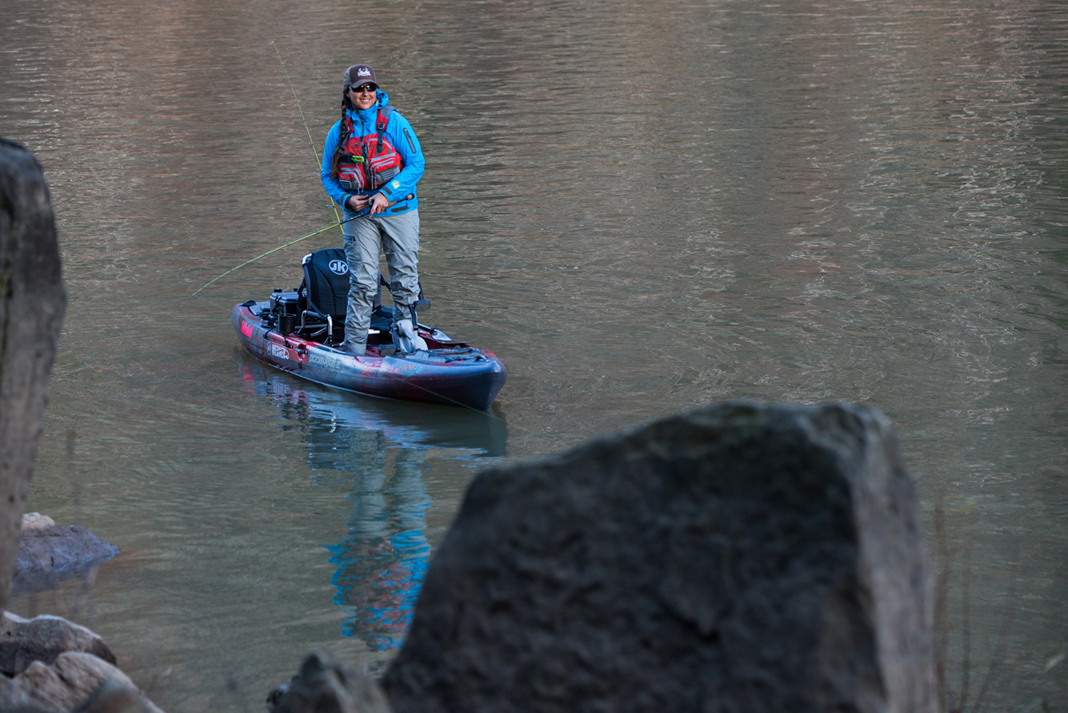 Man standing on kayak and fishing