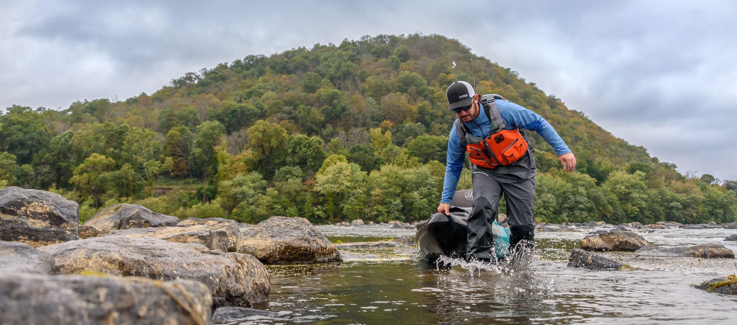 Man wearing PFD and dry pants and dragging his kayak through shallow water