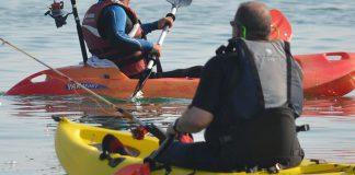People paddling small, plastic fishing kayaks
