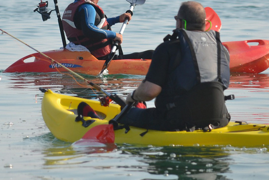 People paddling small, plastic fishing kayaks