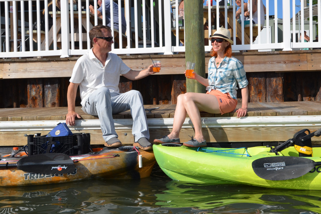 A couple has drinks on the dock by their fishing kayaks