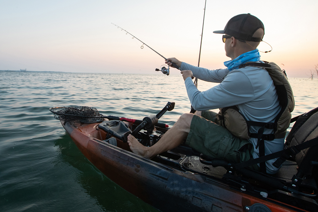 Man casting fishing rod from pedal drive sit-on-top fishing kayak.