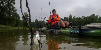 A man reels in a crappie while winter kayak fishing