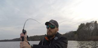 Man in a kayak winds up demonstrate how to cast a baitcaster