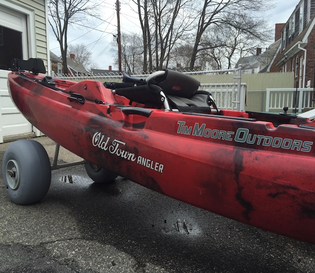 A red Old Town Fishing Kayak sits outside on a homemade kayak beach cart