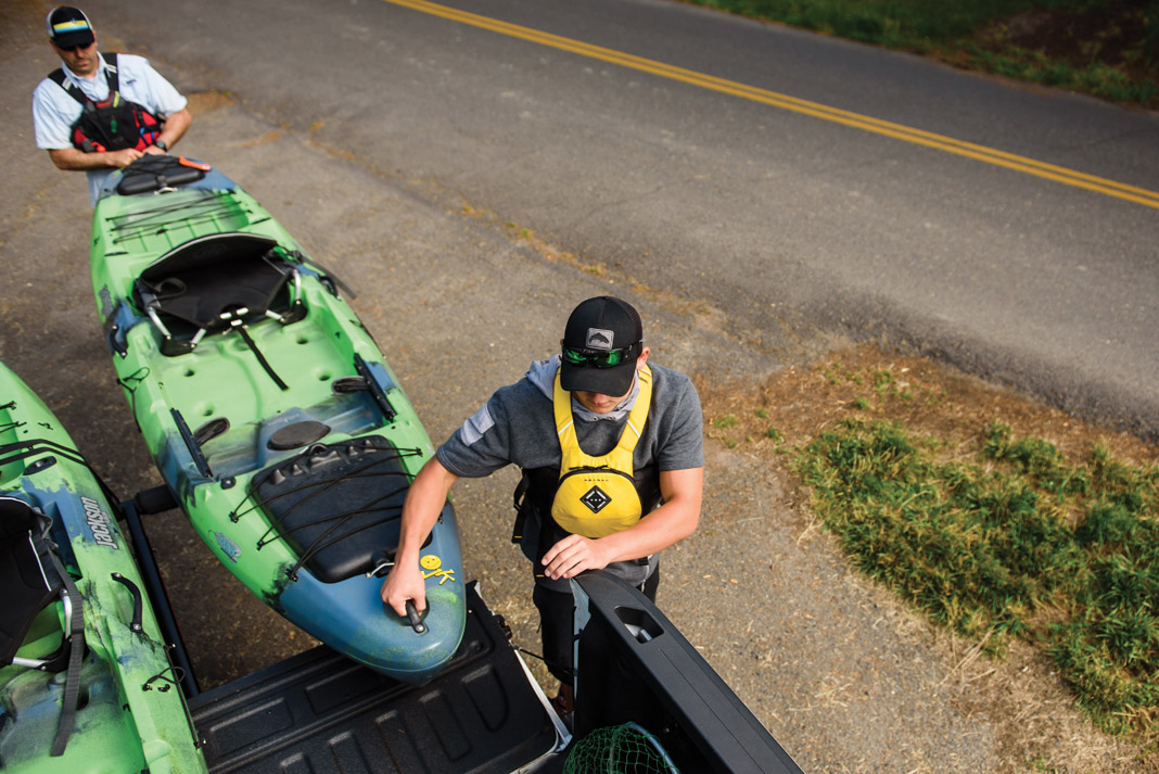 man uses a truck bed extender to transport his fishing kayaks