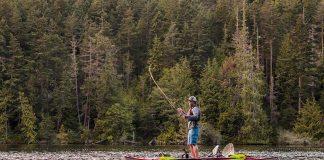 Man standing on kayak while fly fishing.