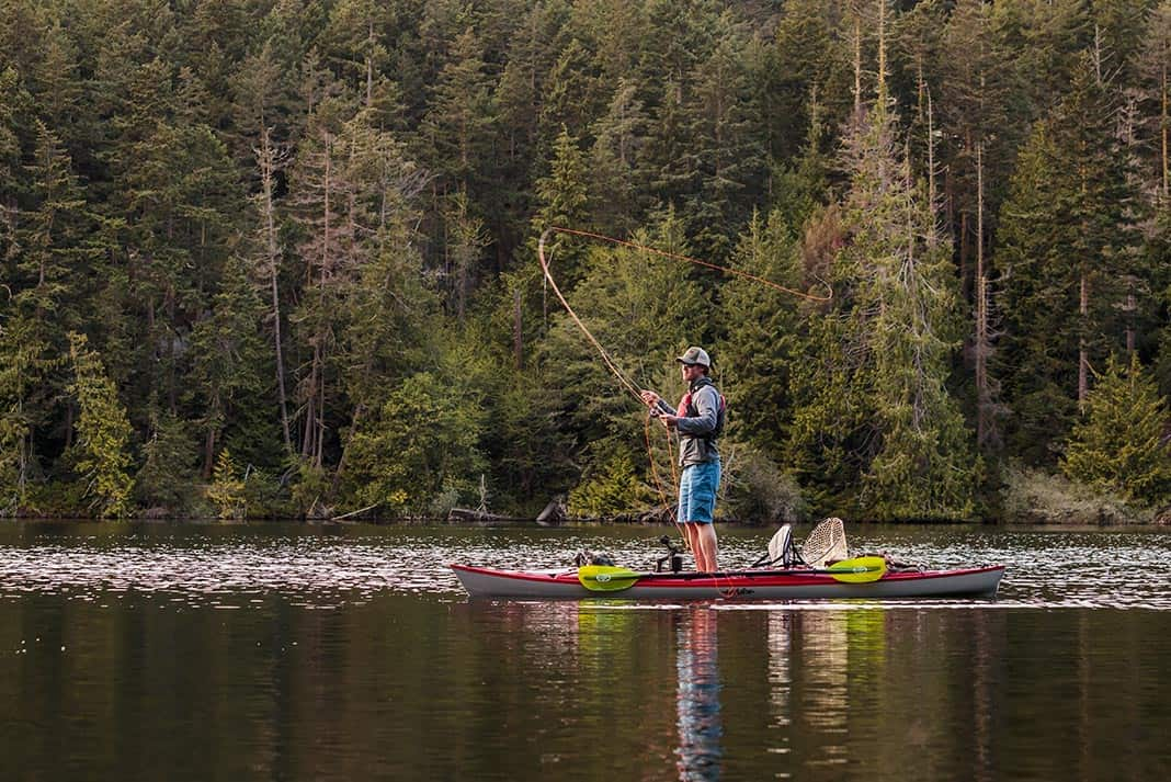 Man standing on kayak while fly fishing.