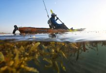 Man paddling ocean fishing kayak with rod behind seat.