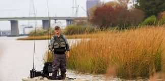 A fisherman stands and fishes among the grass in a Bonafide RS117 kayak