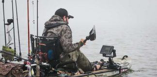 man paddles a fishing kayak with the best fish finder