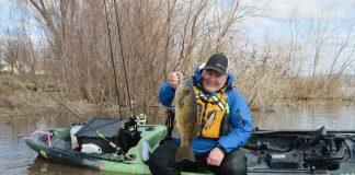 Angler holding up bass on side of kayak