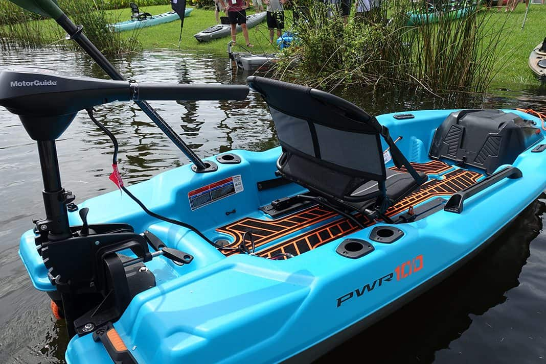Blue fishing kayak with trolling motor on the back in the water