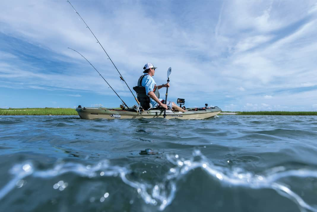 A man on a fishing kayak using a fish finder from Garmin