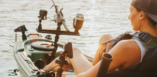 woman on fishing kayak with various mounts and tracks for gear