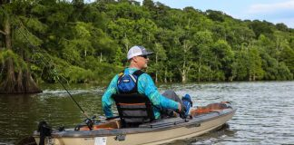 Man pedals on a river in a Pelican Catch 130 HyDryve fishing kayak