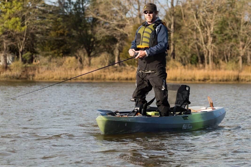 man standing on an Old Town Canoe kayak fishing