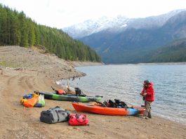 kayak anglers prepare on the shore of Ross Lake in Washington