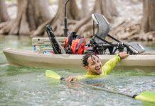 man swims alongside his fishing kayak after flipping it