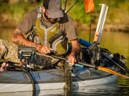 A fisherman in a kayak wearing a PFD, your best tool to prevent paddlesports deaths