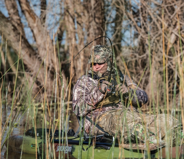 Man wearing camouflage fishing on kayak