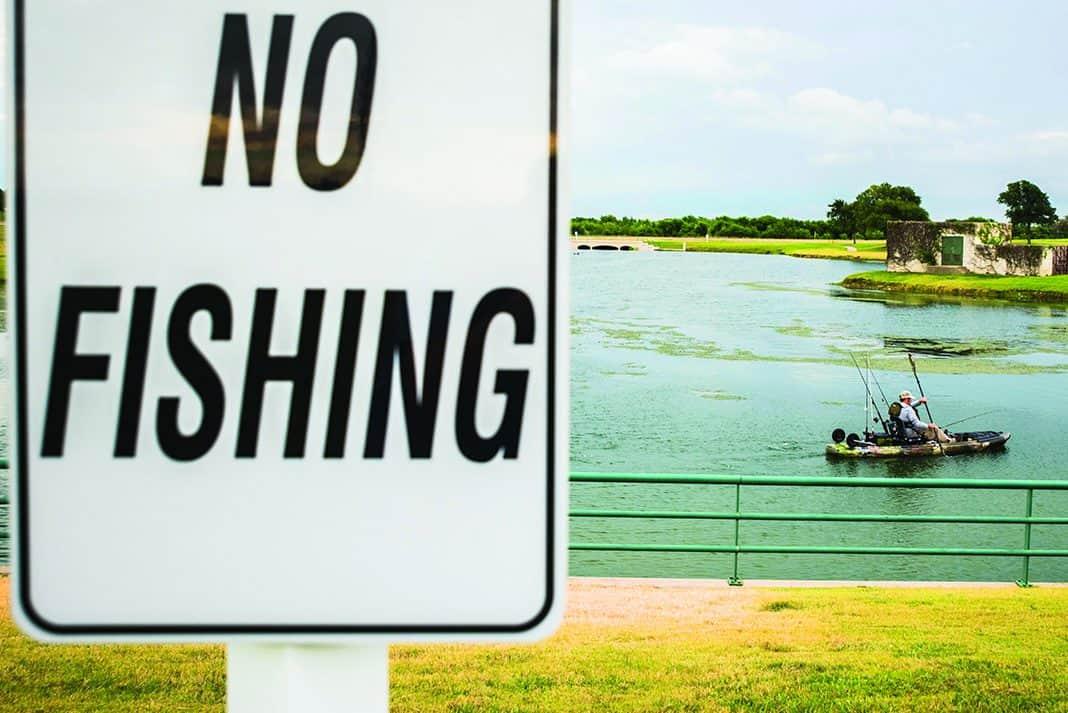 """Kayak Angler fishing behind a """"no fishing"""" sign."""