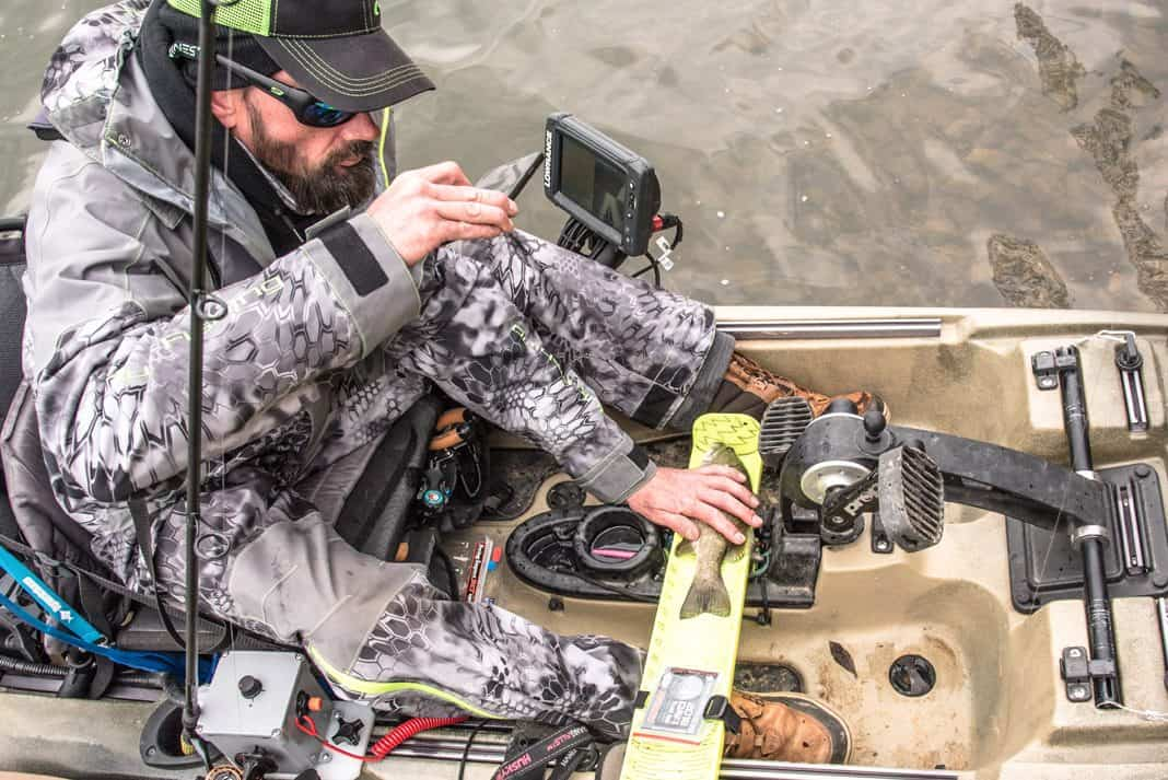 Angler measuring a fish and taking a picture of the fish for a fishing log