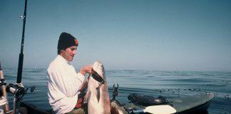 Adam Traubman holding a large fish from his fishing kayak