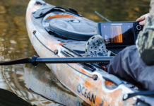 Man looks at a side-imaging sonar in his fishing kayak