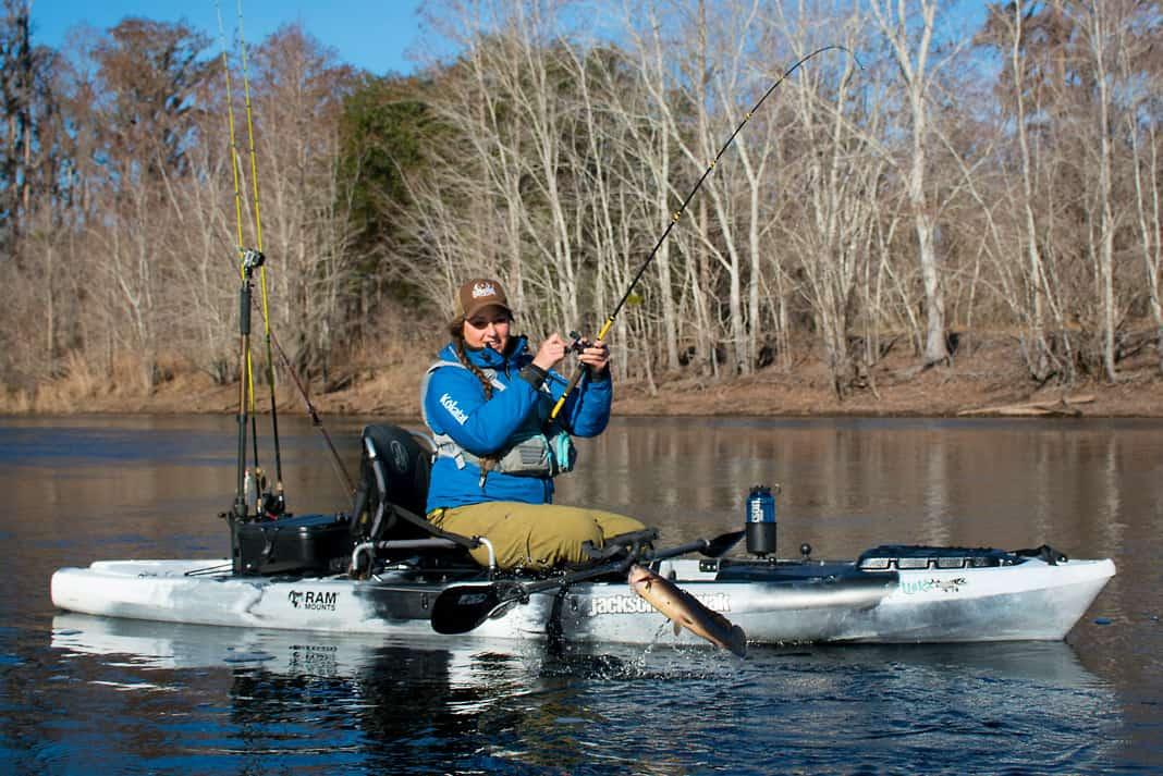 Woman winter kayak fishing for bowfin