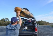 man loads his fishing kayak onto a roof rack for transport