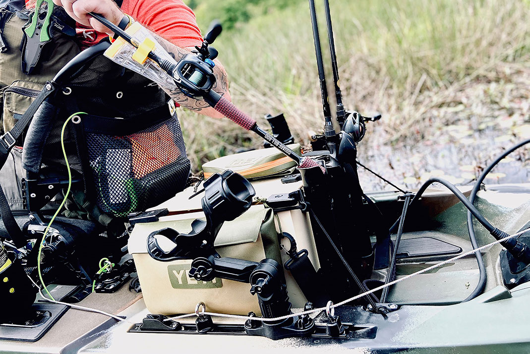 a fishing kayak is equipped with several rod holders of different types