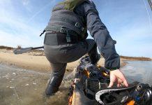 Detail of man getting into fishing kayak at shoreline