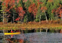 Man in red coat fishes on autumn lake from a yellow kayak