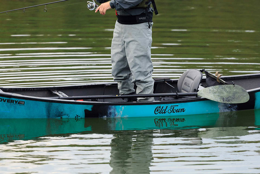 Man stands up to fish in the Old Town Discovery 119 Solo Sportsman canoe-kayak hybrid