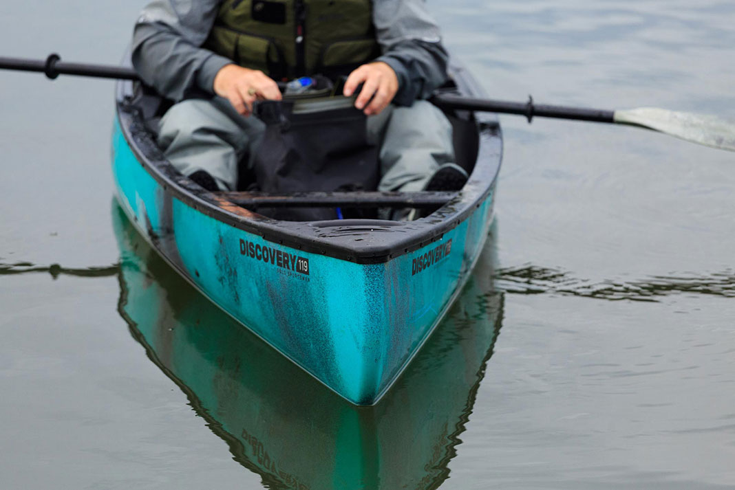 Man sits in an Old Town Discovery 119 Solo Sportsman canoe-kayak hybrid