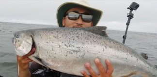 fisherman holds his catch while kayak fishing for king salmon