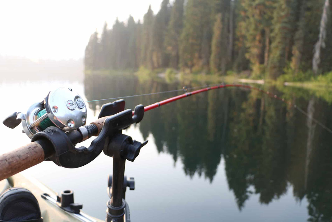 Adjustable rod holders mounted on a kayak with fishing rod over a calm lake