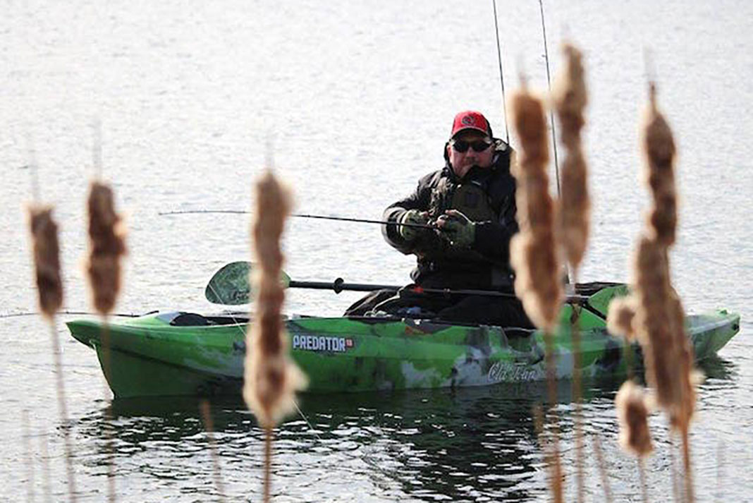 man kayak fishing in front of cattails