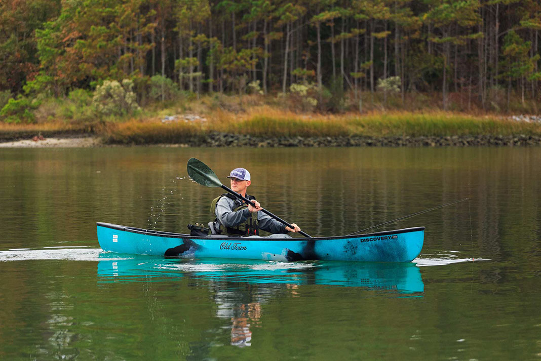 angler paddles the Old Town Discovery 119 Solo Sportsman canoe-kayak hybrid