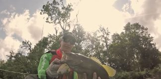 Kayak angler holds up a fish in still image from Small Town Smallmouth bass fishing video