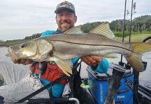 Man holds up large catch from his fishing kayak in Daytona Beach