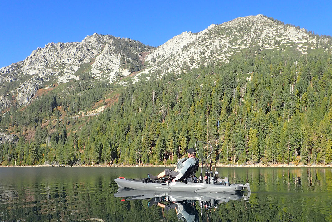 Man paddles past a forested mountain on Lake Tahoe, one of Google's most popular fishing destinations