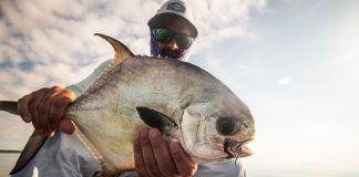 Man holds permit fish up to the camera from his fishing kayak in Key West, Florida